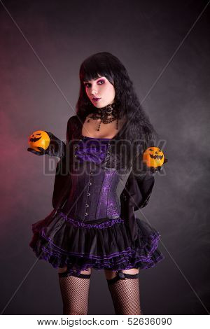 Pretty witch in purple Halloween costume holding Jack-o-lantern style oranges