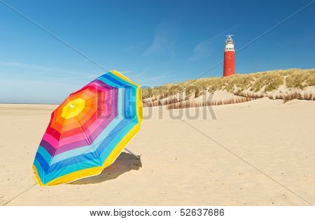 lighthouse with colorful parasol in front on Dutch wadden island Texel