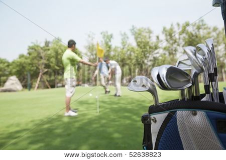 Three friends playing golf on the golf course