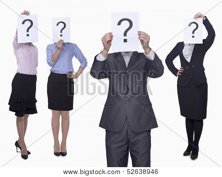 Four business people holding up paper with question mark