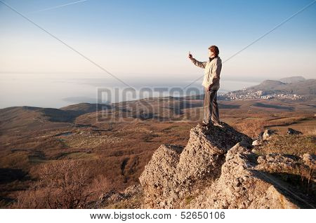 Man with mobile phone on the top of world