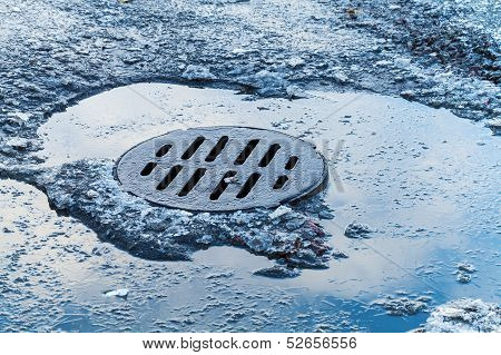 Frosted Puddle With Round Old Sewer Manhole