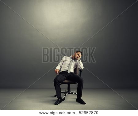 bored businessman sitting in the empty dark room