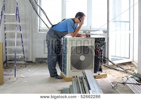 A worker sets air conditioner in apartment and talking on the phone