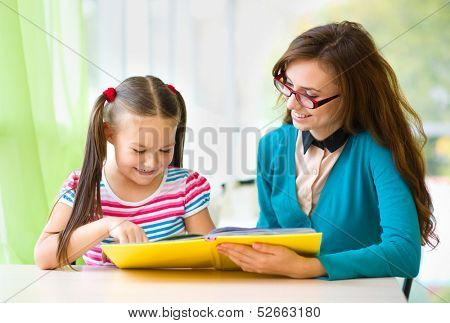 Mother is reading book with her daughter, indoor shoot