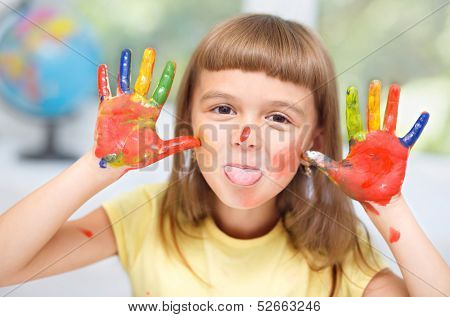 Portrait of a cute cheerful girl showing her tongue and hands painted in bright colors