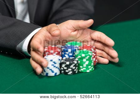 "Poker player going ""all in"" pushing his chips forward. Symbol of addiction to the poker"