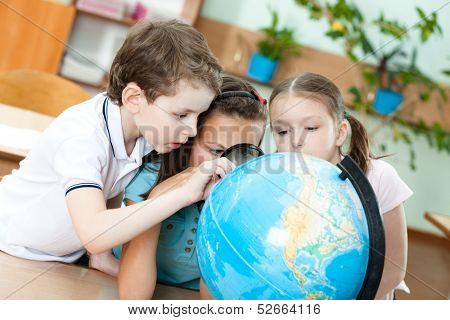 Three friends examine a school terrestrial globe