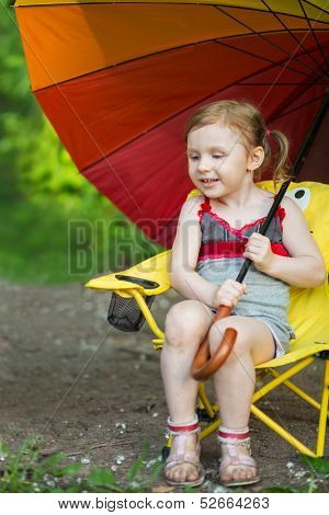 Little girl with a grimy legs sitting on a chair with a large colorful umbrella