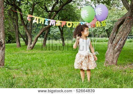 Little girl stands in park, holding three air balloons in her hand, happy birthday sign behind her back