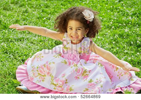 Little mulatto girl sits with outstretched hands to sides on grassy lawn spreading hem of her dress