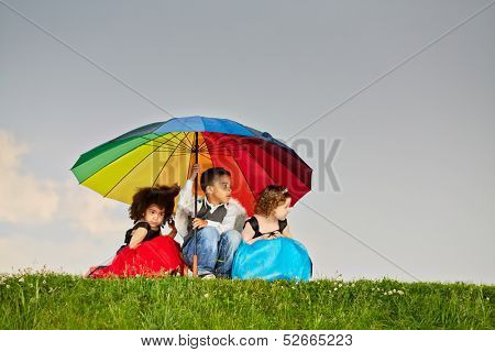 Little boy and two little girls hide from rain sitting squatted under big colorful umbrella
