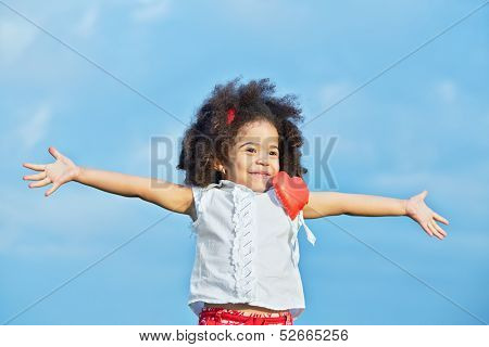 Half-length portrait of smiling little girl in red shorts and white t-shirt with pinned red heart with her arms outstretched to sides