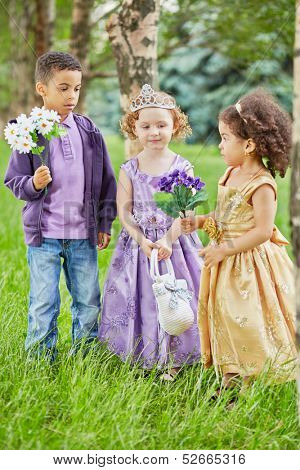 Boy and two little girls dressed in party frocks stand in park on grassy lawn, boy and one of girl hold flower