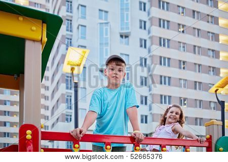 Boy and his younger sister having fun on children playground in house yard
