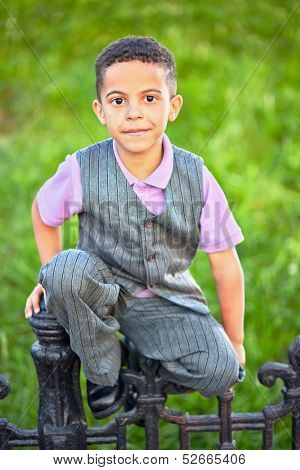 Little boy dressed in suit with vest sits on black wrought-iron fence