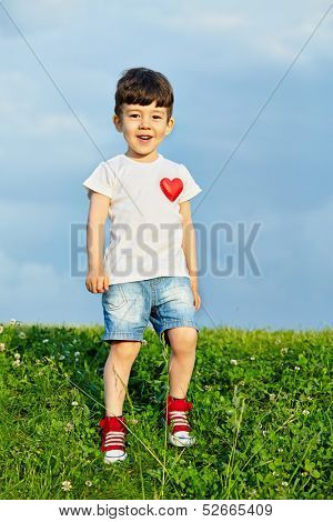 Little boy in shorts and white t-shirt with pinned red heart goes down grassy slope