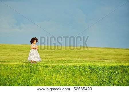 Little mulatto girl stands alone on meadow against sky