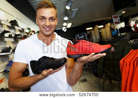 Young handsome man choosing sport footwear in sport outlet