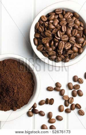 top view of coffee beans and ground coffee in bowls