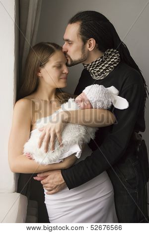 Young Family With The Baby At Home