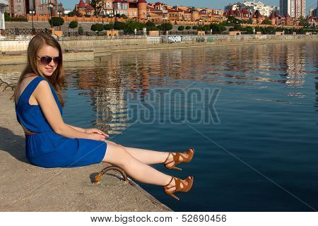 girl in a blue dress on the background of the river. Ukraine. Kiev. Obolon