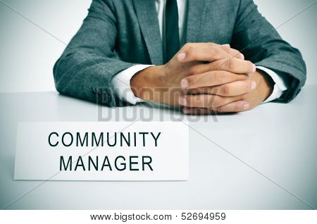 a man wearing a suit sitting in a desk with a signboard in front of him with the sentence community manager written in it