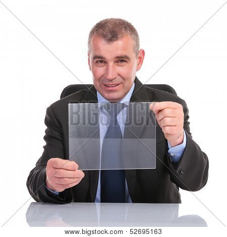 business man sitting at his desk and presenting a transparent pannel while smiling for the camera. on a white background