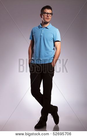 full length picture of a young casual man looking away from the camera while keeping his hands in his pockets. on white background