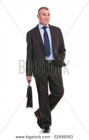 full length photo of a business man walking toward the camera with a briefcase in his hand while looking away. on a white background