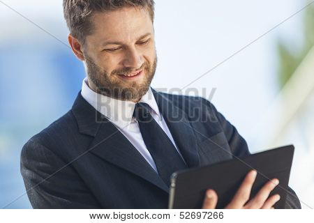 A smart young businessman with a beard using a tablet computer
