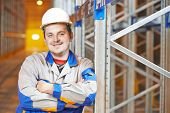 young smiling warehouse worker in uniform near rack stack in storehouse