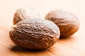 stock photo of mace  - Mace spice scattered on wooden table close up  - JPG