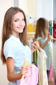 Beautiful girl choose blouses near mirror on room background