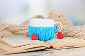 image of blue things  - Cup with knitted thing on it and open book close up - JPG