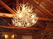 picture of log cabin  - chandelier made of antlers hanging in a rustic cabin - JPG