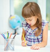 Little girl is drawing using color pencils while sitting at table