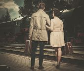 stock photo of passenger train  - Beautiful vintage style couple with suitcases on  train station platform - JPG