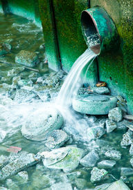 picture of gushing  - Some polluted water sewage or waste product gushing from a pipe into the river - JPG