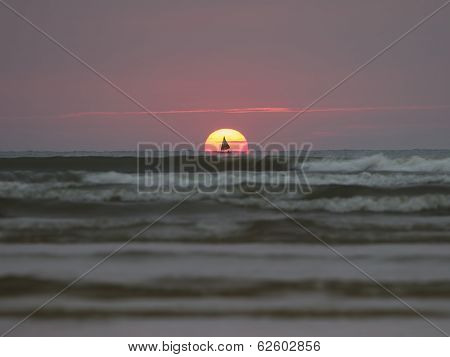 Sailing Boat And Sun Rising In Sea