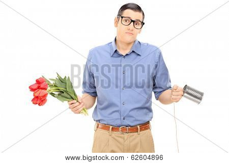 Confused man holding flowers and a tin can phone isolated on white background