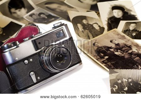 The old film camera and ancient photos on a white background.