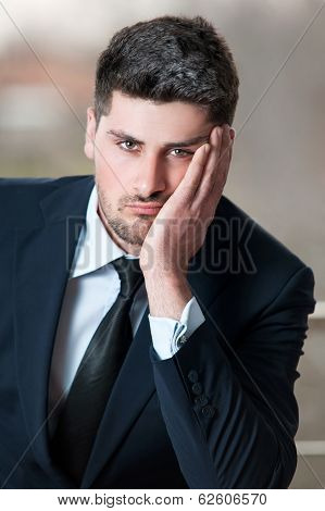 Portrait of a sad businessman in black suit and stress, problem, crisis concept - stressed