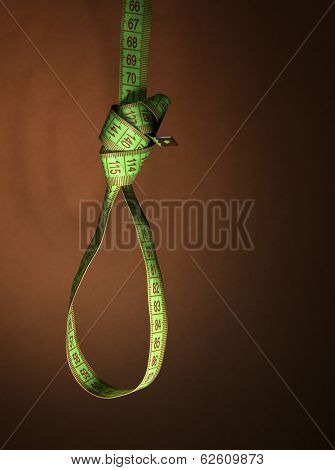 Tape measure noose on brown background - diet concept