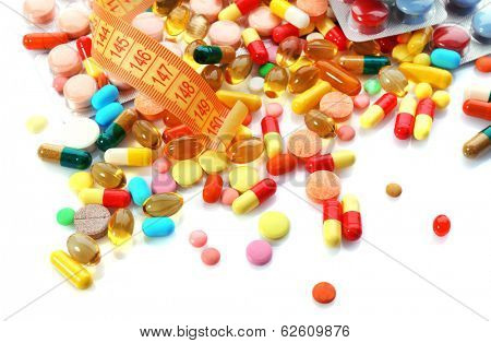 Measuring tape and pills, isolated on white. Dieting concept