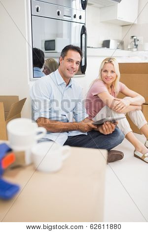 Portrait of a smiling couple using digital tablet amid boxes in a new house