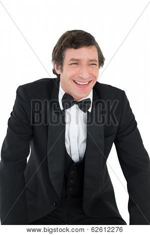 Smiling groom looking away over white background