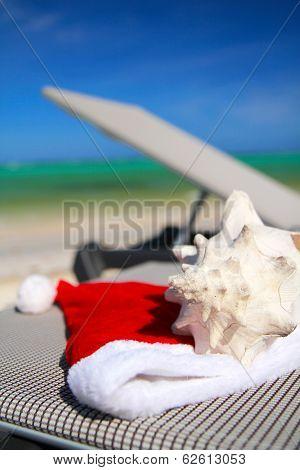Santa Hat And Seashell On Chaise Longue
