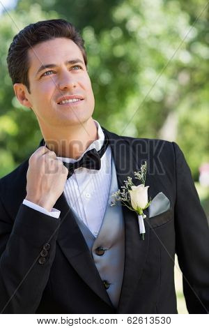 Nervous bridegroom looking up in garden