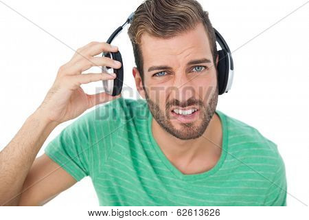 Portrait of a irritated young man with headphones over white background